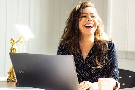 woman at laptop laughing