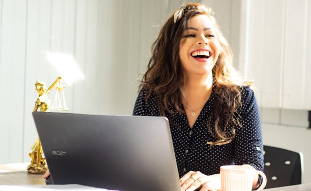 woman at laptop laughing