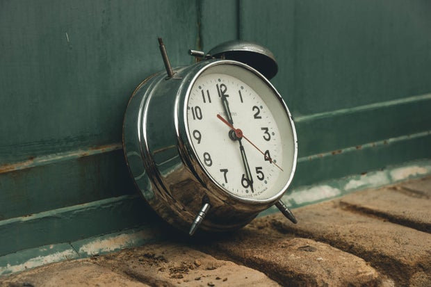 Old alarm clock with green background