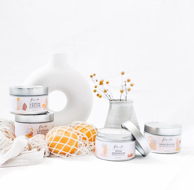 Body butters and lip balms are displayed against a white backdrop with some plants.