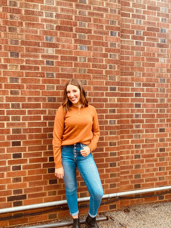 Girl posing against brick wall