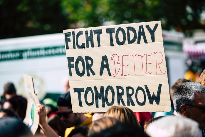 """cardboard sign being held up that says """"Fight Today For A Better Tomorrow"""""""