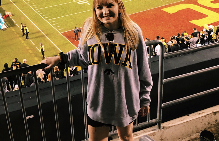 girl standing in the bleachers at a football game