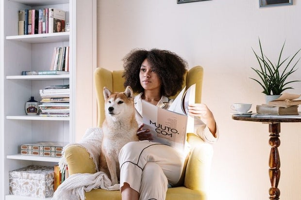 woman sitting with magazine and dog in the morning