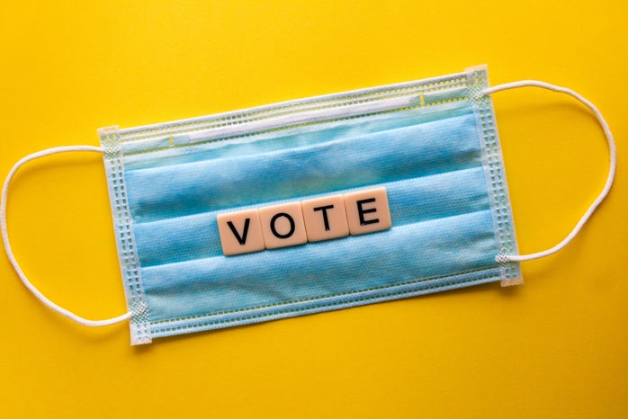 """blue mask with tiles spelling """"vote"""" in front of yellow background."""