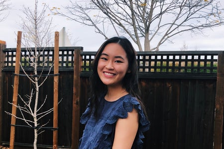 Girl in a blue top is smiling in front of a fence