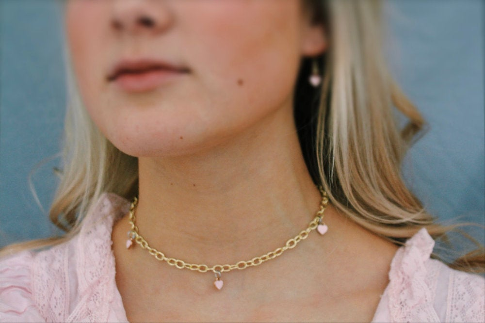 blonde girl wearing gold necklace with pink hearts from Millie's Boutique
