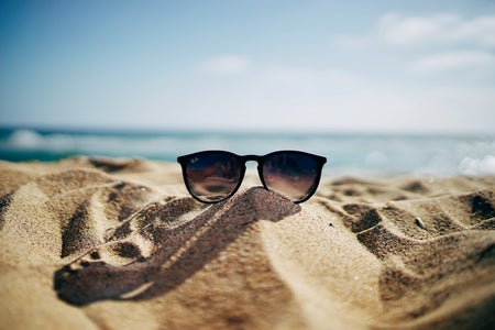 raybans glasses sitting on top sand