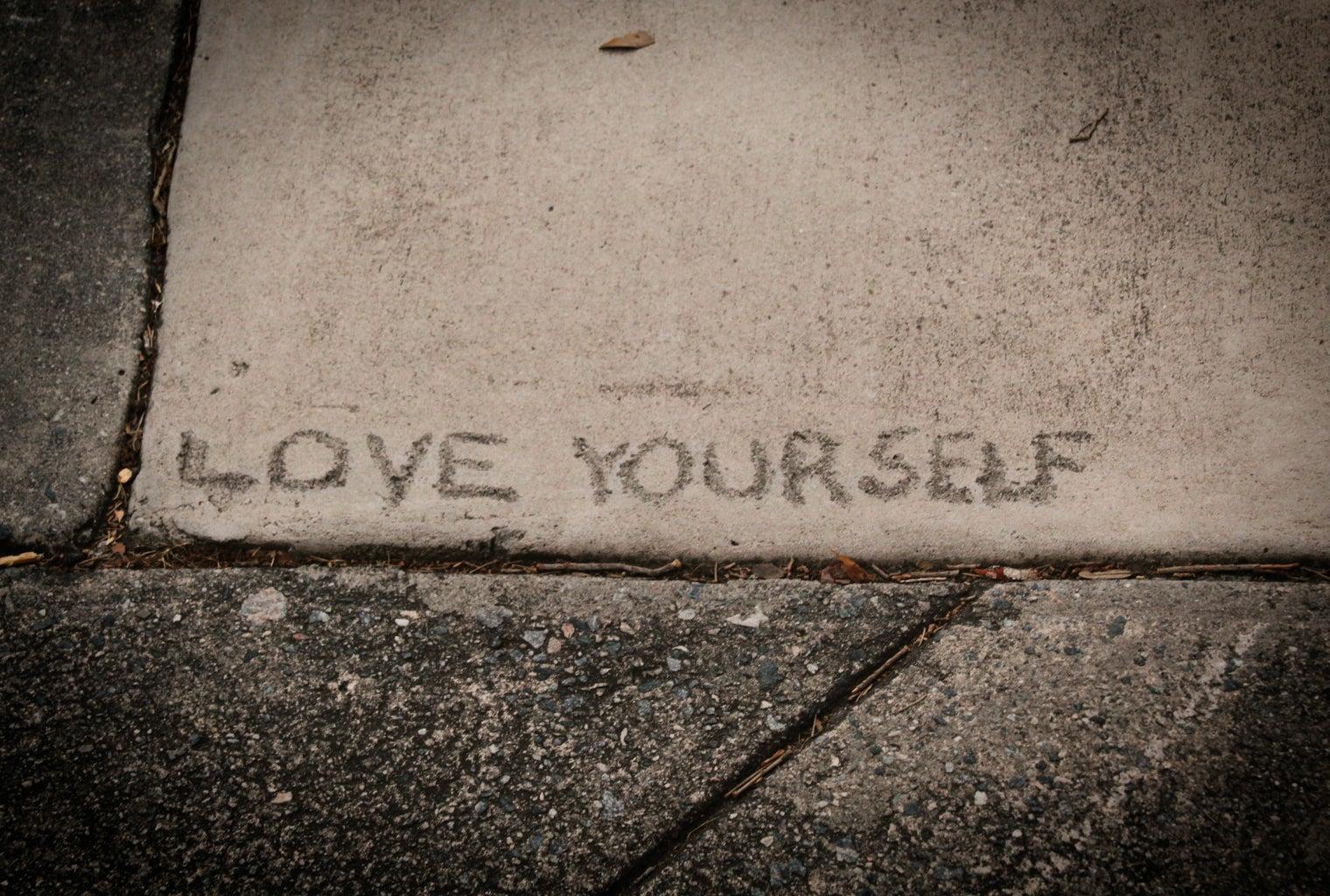 love yourself written on a sidewalk