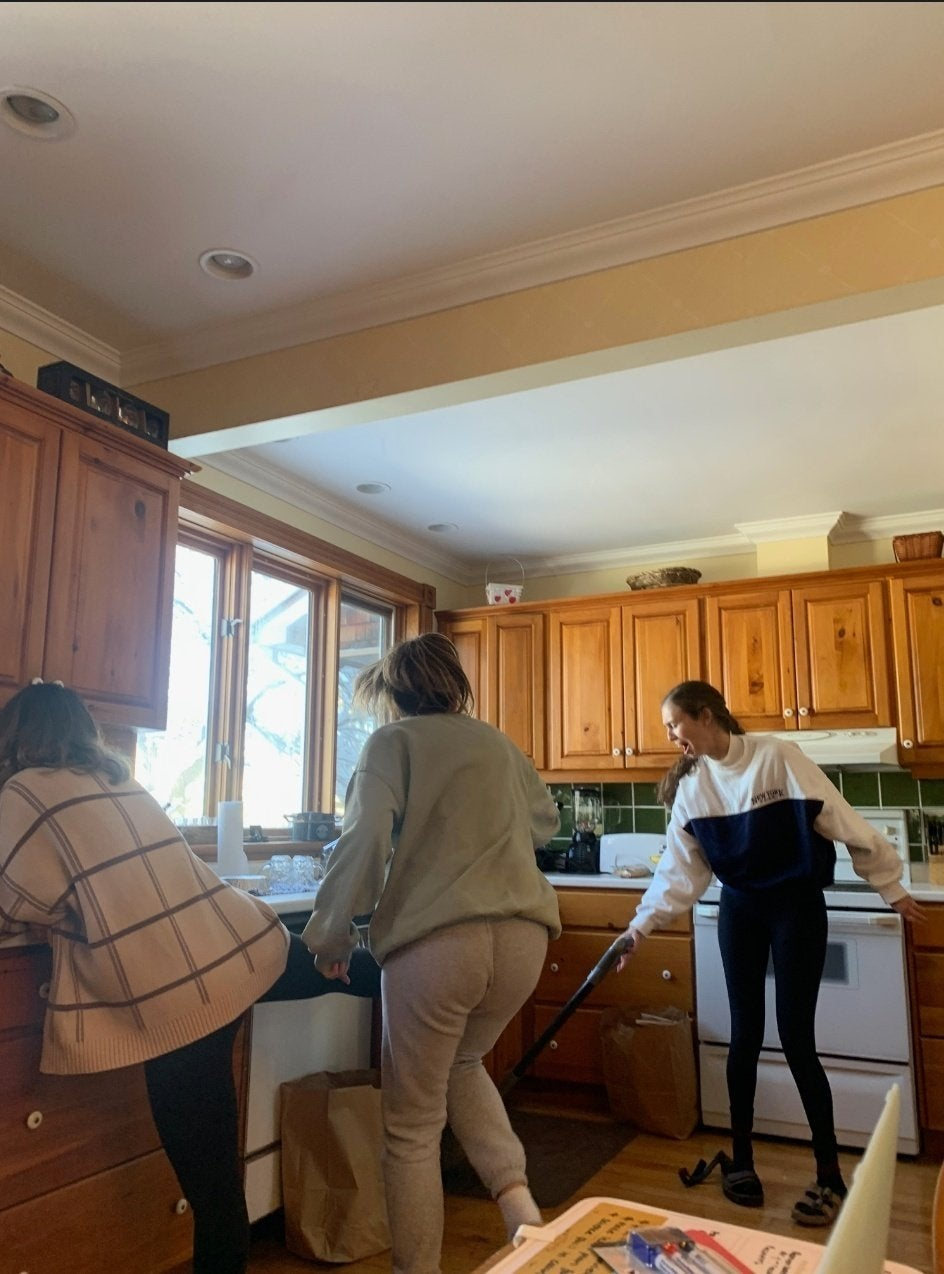 This is a picture of girls cleaning in a kitchen made of wood; girls pictured are Rachel Alter, Sasha Folgoas, Daphna Roytblat