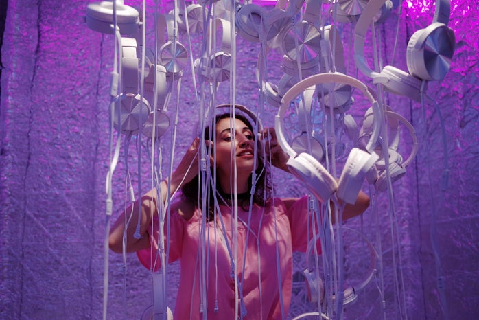Woman wearing headphones in a purple background