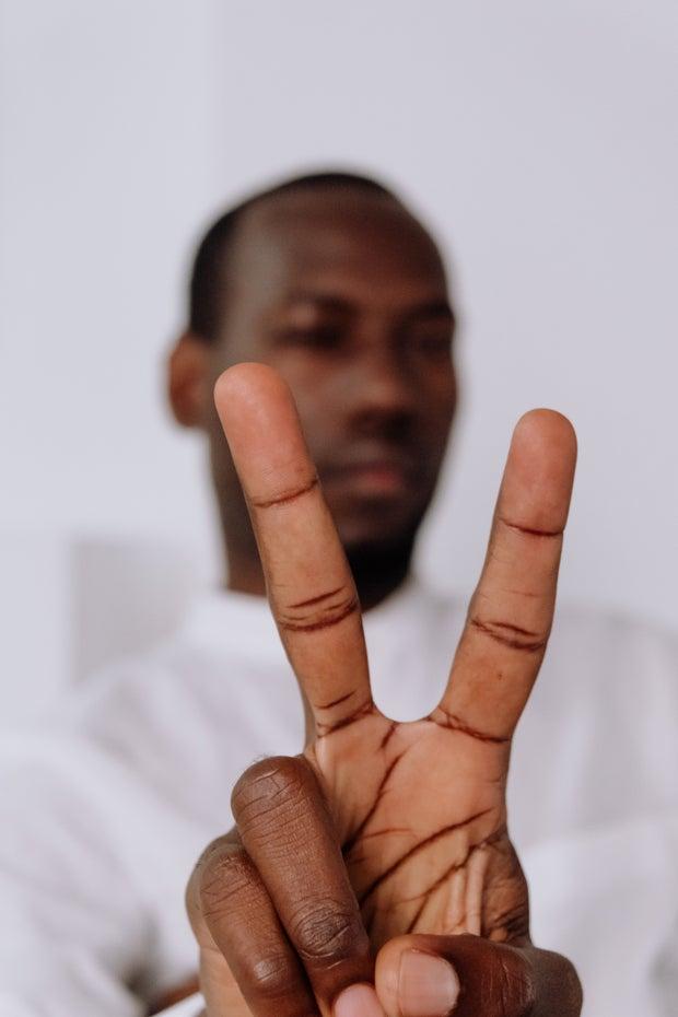 man holding up sign language for letter V