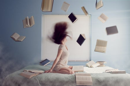 woman sitting on bed surrounded by books