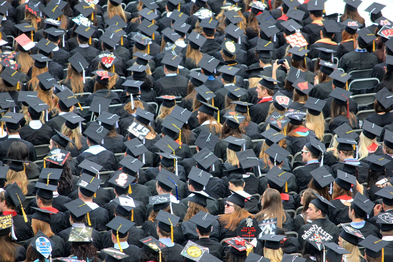 a crowd of people sitting at a graduation all wearing graduation caps