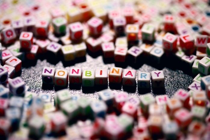 Non-binary written in yellow green and red logo blocks