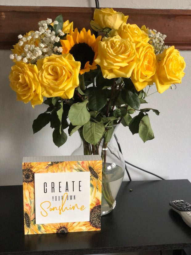A bouquet of yellow roses with a single sunflower and a plaque.