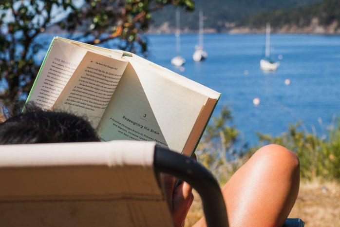 person reading book in chair relaxing with ocean in the distance