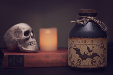 white skull on a book with a potion