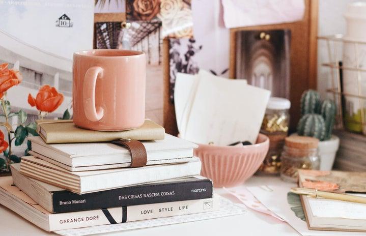 Pink desk with books and mug