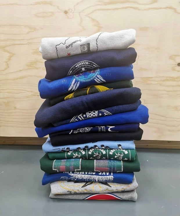 Photo is of a pile of folded Vintage sweaters
