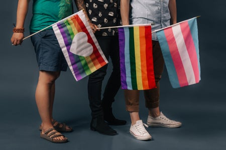 Three people holding three different LGBTQ+ pride flags.