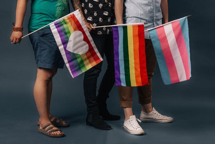 Three people holding three different LGBTQ+ pride flags.