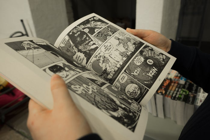 Hands holding a japanese comic book.