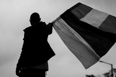 Man waving Nigerian flag, protesting against SARS