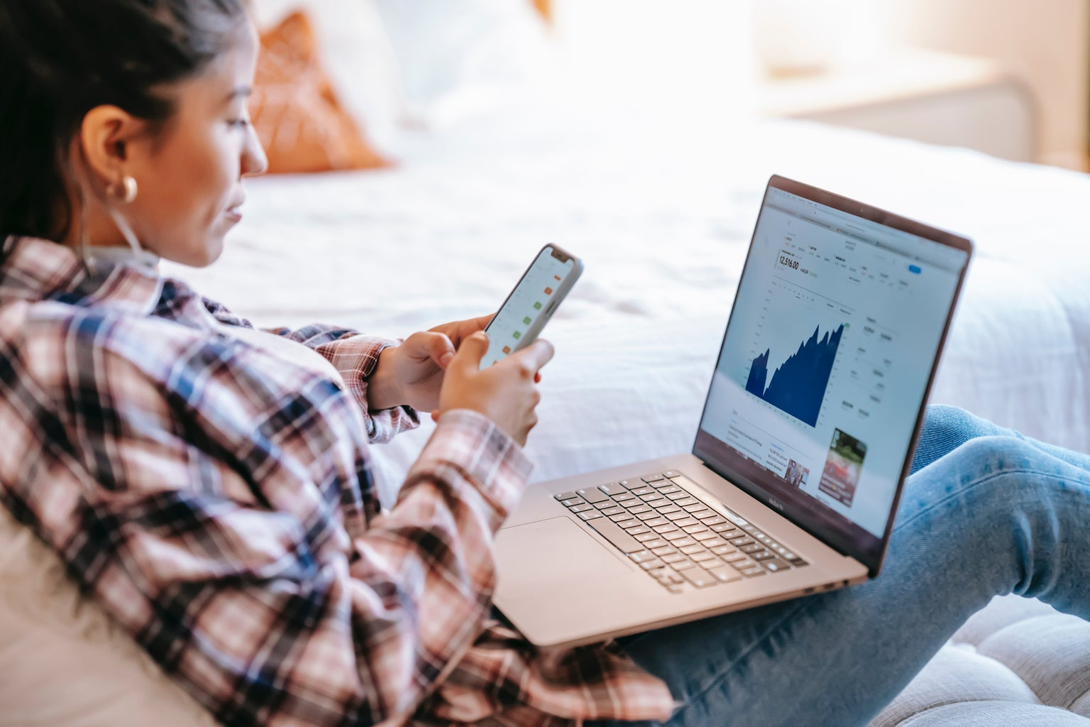 woman on phone and laptop looking at stocks