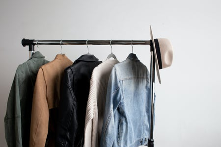 rack of clothes with five jackets and a hat