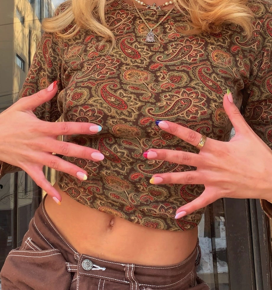Picture of girl's hands with colorful nails in front of torso