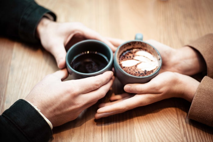 two cups of hot chocolate on table being held