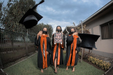 graduates wearing masks in cap and gowns