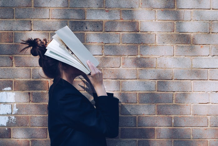 A woman covers her face with a book in front of a brick wall