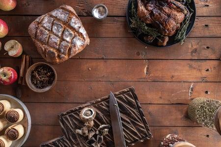 roasted turkey, bread, and cinnamon rolls on a table