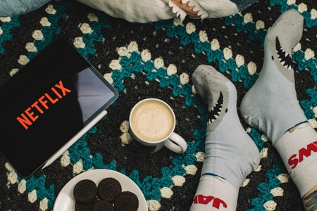 Screen with Netflix Logo, plate of cookies, coco, and shark Socks