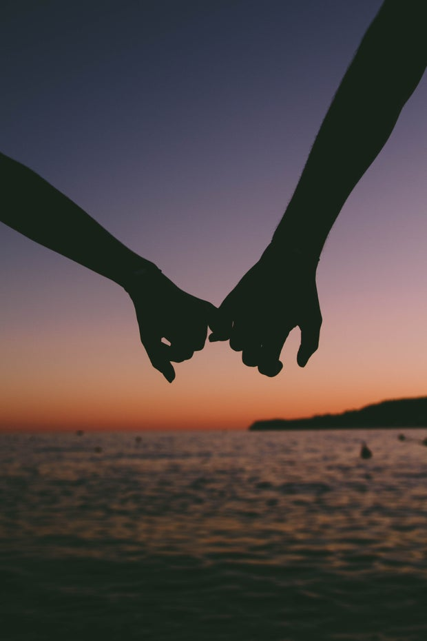 holding hands at sunset
