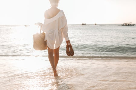 women in white dress holding brown woven basket on beach