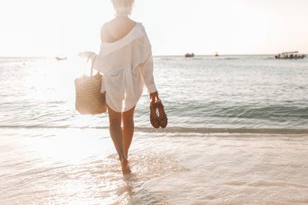 women in white dress holding brown woven basket on beach