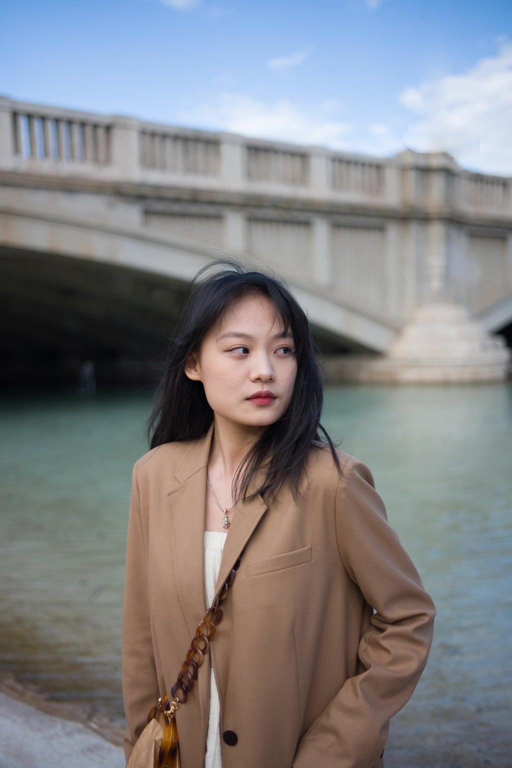 woman in blazer standing in front of bridge over river