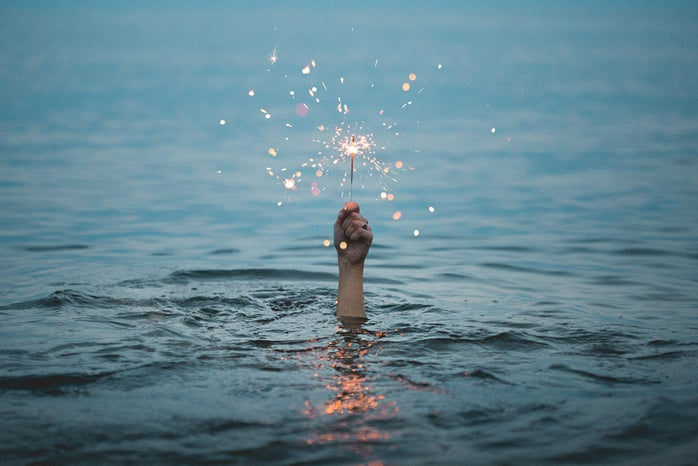 person in water holding a sparkler