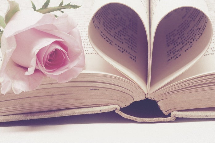A flower on top of a books with pages folded into a heart