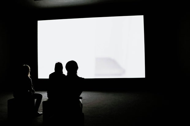 Silhouettes watching TV on a white screen