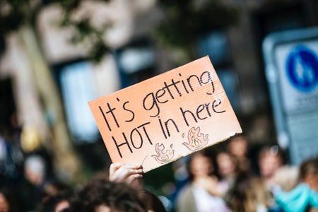 "person holding a sign that says ""it's getting hot in here"""