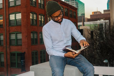 Black Poet Gabriel Angrand sitting, wearing glasses, in blue jeans, light-blue button-up, and green hat, holding a book in his hands.