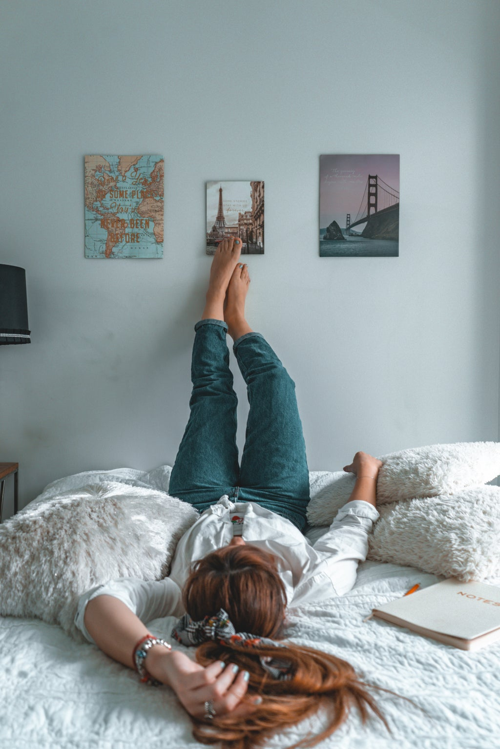 Woman on her bed with her feet up on her wall filled with posters.