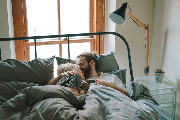 Couple kissing on forehead in bed
