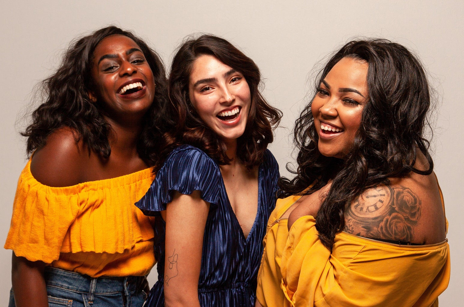 Three women laughing at the camera