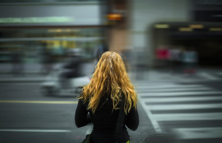 woman standing facing blurry street