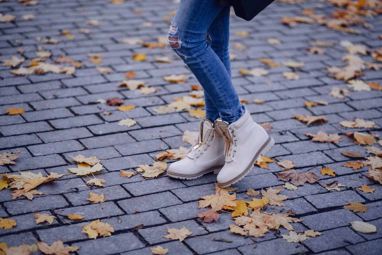 person wearing boots in fall leaves